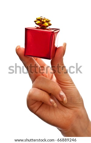 Woman's hand with a small red gift box with gold bow isolated on white background - stock photo