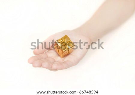 woman's hand with a small yellow gift - stock photo