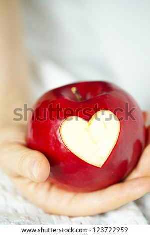 Woman's hand with apple, which cut a heart - stock photo