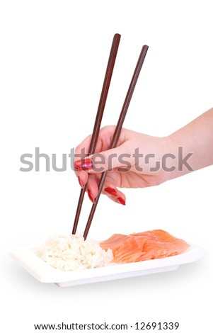 Woman's hand with chopsticks and plate with rice and raw red fish