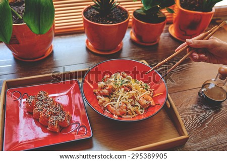 Woman's hand with chopsticks reaching for rice noodles and sushis, delicious and easy lunch.  - stock photo