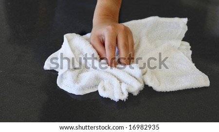 Woman's hand with cotton terry towel wiping stone counter - stock photo