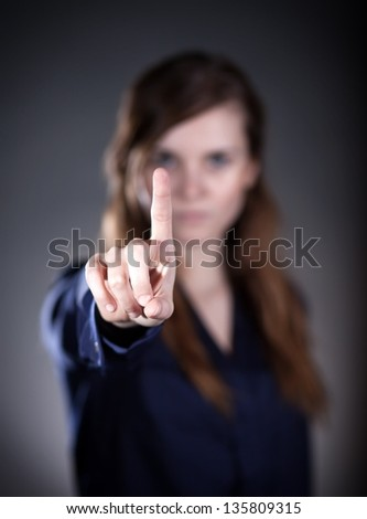 Woman's hand with finger on dark background - stock photo