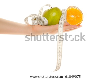 Woman's hand with green apple, orange and tape measure isolated on white - stock photo
