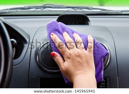 Woman's hand with microfiber cloth polishing  a car  - stock photo
