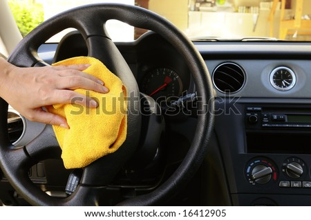 Woman's hand with microfiber cloth polishing steering wheel of an SUV car