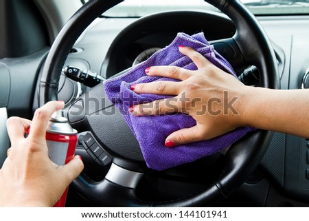 Woman's hand with microfiber cloth polishing wheel of a car - stock photo