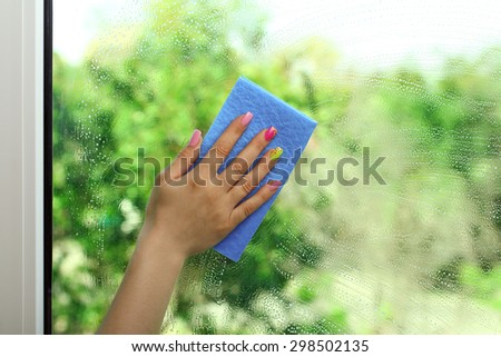 Woman`s hand with napkin  wipes soap window on a background of trees - stock photo