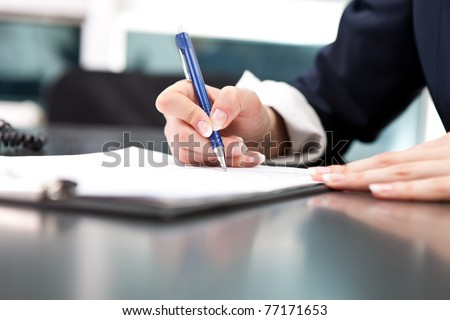 woman's hand with pen signing document, close up - stock photo