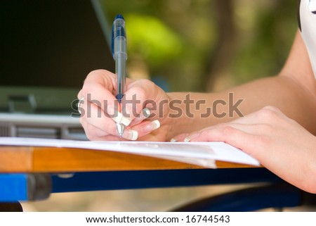 Woman's hand with pen writing down notes with laptop on background - stock photo