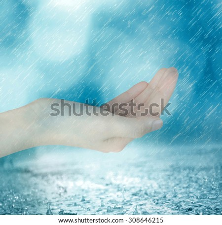 Woman's hand with rain. Conceptual image of sharing, giving, offering, taking care and protection - stock photo