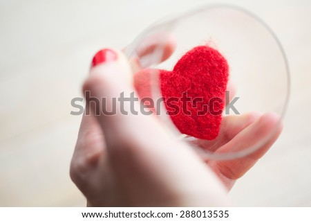 Woman's hand with red nails is holding glass with red felt heart. A gift for Valentine's Day
