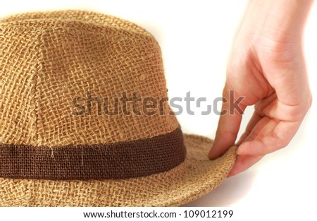 Woman's hand with summer straw hat on white background - stock photo