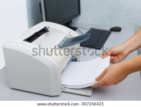 Woman's hand with working copier - stock photo