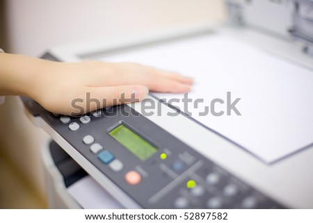 Woman's hand with working copier