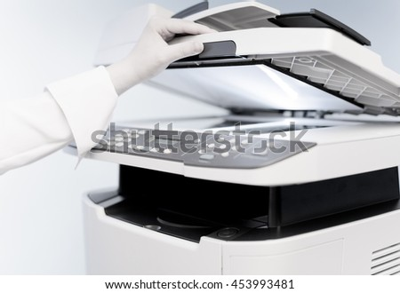 Woman's hand with working copier (focus on finger) - stock photo