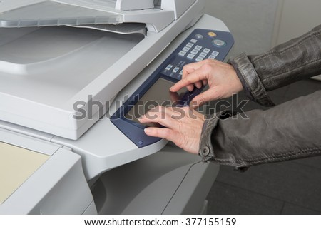 Woman's hand with working copy machine at office, good job - stock photo
