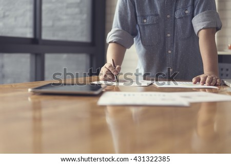 woman's hand working with business document and tablet for working concept, selective focus and vintage tone