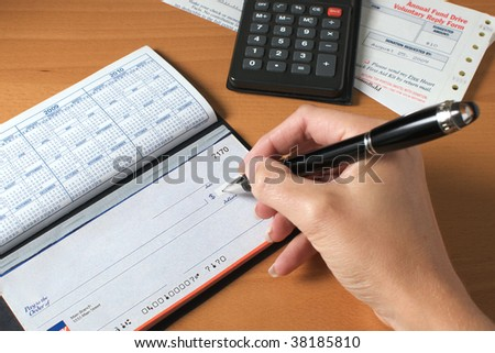 Woman's hand writing a check to pay the bills, with calculator and an invoice on the desktop. - stock photo