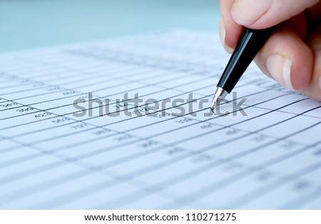 woman's hand writing entries in a notebook