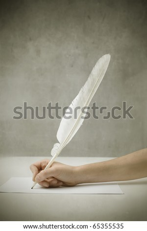Woman's hand writing with a plume - stock photo