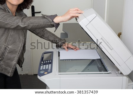 Woman's hands and body with working copier  - stock photo