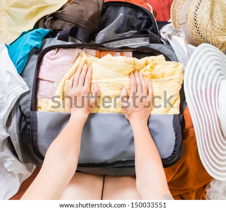 Woman's hands are packing clothes in a bag. Top view. - stock photo