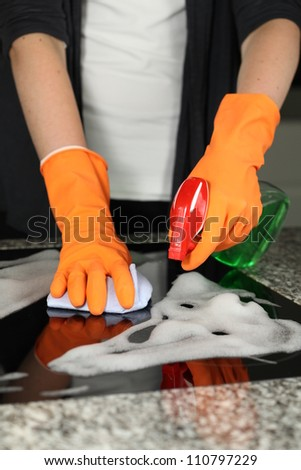 Woman's hands cleaning a kitchen stove, closeup - stock photo