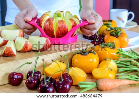Woman's hands cutting apple with cutlery equipment, variety fruits in colorful modern kitchen / healthy lifestyle conceptual