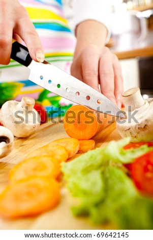 Woman's hands cutting carrot, behind fresh vegetables.