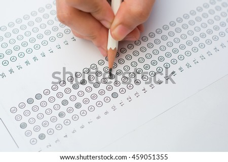 woman's hands filling in standardized test form - stock photo