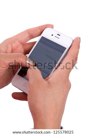 Woman's hands hold a cell phone while texting a message. - stock photo