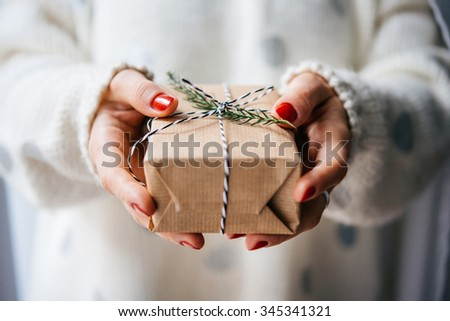Woman's hands hold christmas or new year decorated gift box - stock photo