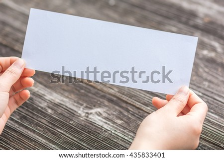 woman's hands hold white blank paper