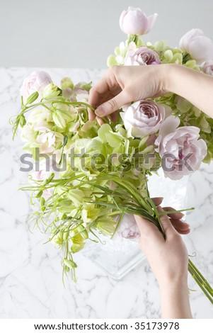 Woman's hands holding a beautiful flower arrangement - stock photo