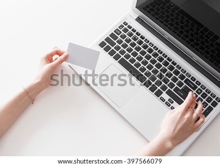 Woman's hands holding a credit card and using laptop for online shopping - stock photo