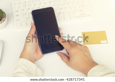 Woman's  hands holding a credit card and using smart phone for online shopping.vintage tone - stock photo