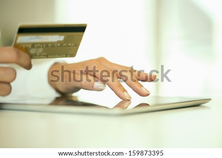 Woman's hands holding a credit card and using tablet pc for online shopping - stock photo