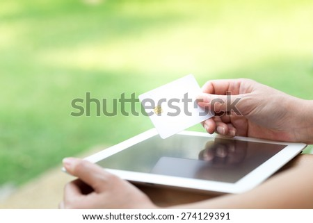 Woman's Hands Holding A Credit Card And Using Tablet PC. Online Shopping Concept - stock photo