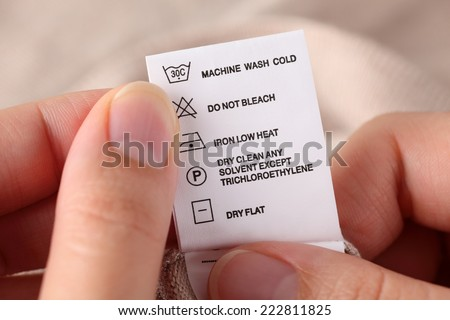 Woman's hands holding clothes label with cleaning instructions. - stock photo