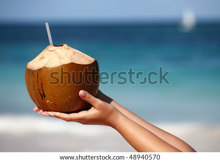 Woman`s hands holding coconut on tropical beach - stock photo