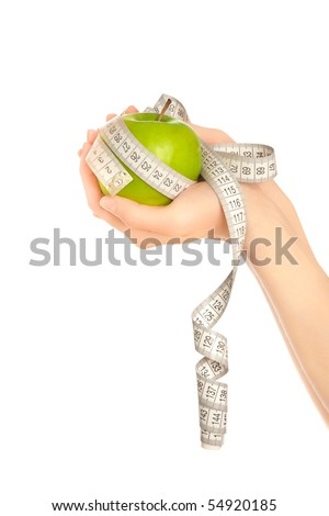 Woman's hands holding green apple with measuring tape isolated - stock photo