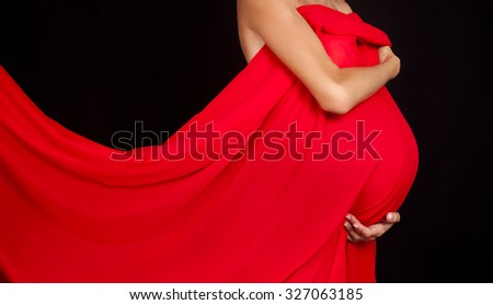 woman's hands holding her pregnant belly wrapped in red cloth - stock photo