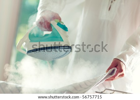 Woman's hands holding hot iron, steaming clothes,shallow depth of field - stock photo