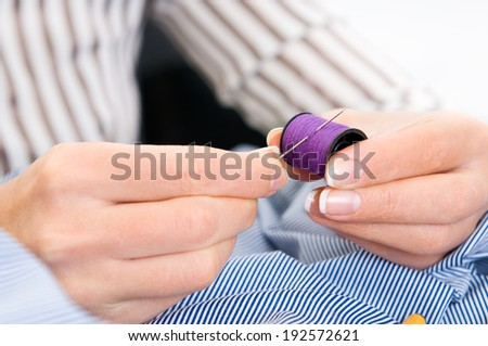 woman's hands holding thread reel over the shirt - stock photo
