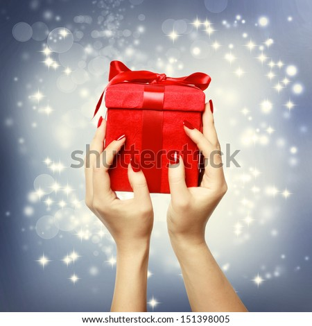 Woman's hands holding up red present box on Christmas on shinning background - stock photo