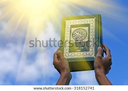 Woman's hands holds Koran - holy book of muslims, on blue sky with clouds. With instagram style filter - stock photo