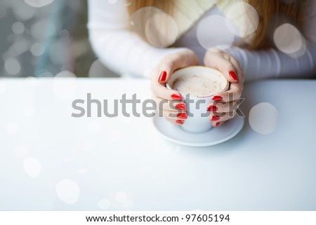 Woman's hands hugging a cup of coffee in a restaurant - stock photo
