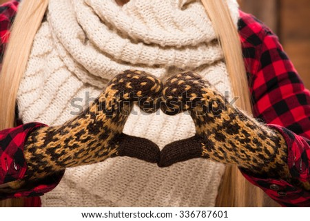 Woman's hands in gloves showing love sign demonstrating warm feeling to close people, parents, relatives, etc.