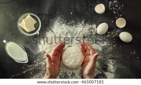 Woman's hands knead dough on table with flour